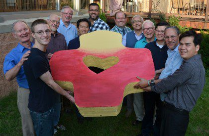 Members of the Dehon Formation Community in Chicago gather for a photo with Frs. José Ornelas Carvalho and John van den Hengel (along with a bigger-than-life SCJ logo!).
