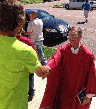Fr. Guy greets a parishioner after Mass