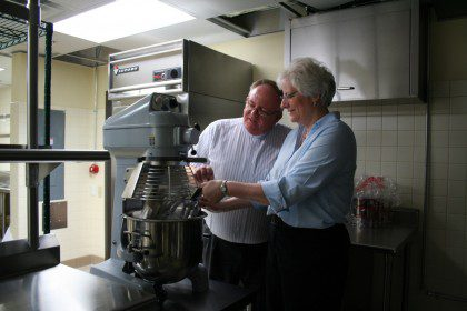 Dn. David and Barb Haag survey new kitchen equipment prior to the opening of Sacred Heart at Monastery Lake. Barb recently left her position as food services director at SHML.
