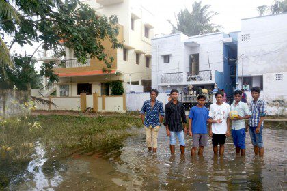 Members of the formation community in Chennai stand in the flooded streets near their home.